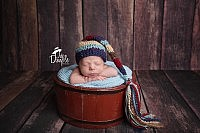 newborn boy in red bucket with wood backdrop