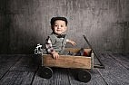 little boy sitting in wooden wagon with drivers hat.